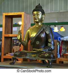 Buddah on metallic golden statue, sitting, square image