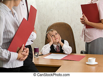 A boy of five at the office desk as a boss