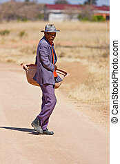 Elderly African man - Old african man crossing dirt road in...
