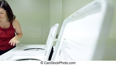 Young woman doing laundry. UHD 4K - Young woman washing her...