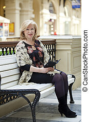 Old woman sitting on a bench in the mall with pad