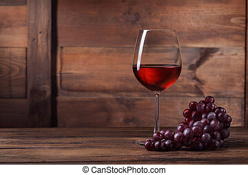 Red wine in glass with grape on wooden background
