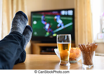 Television, TV watching (football match) with feet on table...