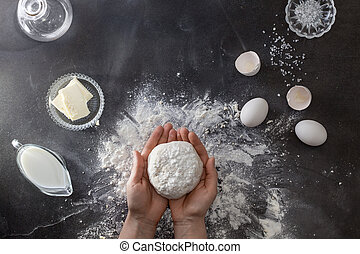 Woman's hands knead dough on table with flour and...