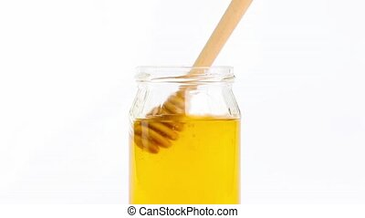 honey jar with dipper on top - opened honey jar with wooden...