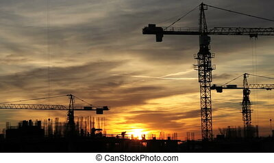 Construction cranes fading from sunset to dusk