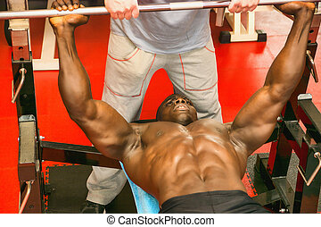 Hunky muscular black bodybuilder working out in gym on bench...
