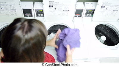 Young woman doing laundry UHD 4K - Young woman washing her...