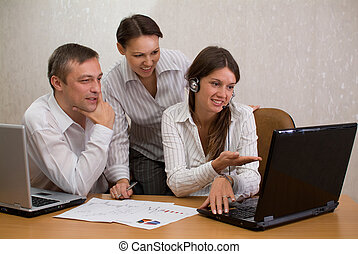 Group of employees in the office with laptops