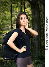 Disoriented Hiking Girl - Portrait of a young woman carrying...