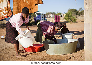 washing clothes - african woman in a poor community washing...