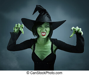Scary witch with green skin performs magic on dark...