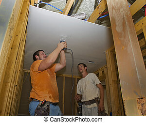 Screwing the Sheetrock - Worker the sheetrock while the...