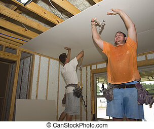 Two sheetrock workers nailing the sheetrock