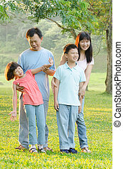 Asian Family Enjoying Walk In Summer Countryside