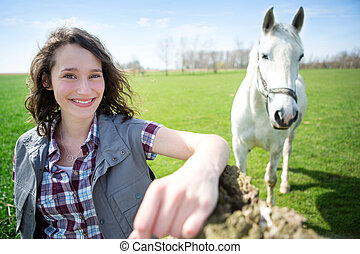 Portrait of a young attractive farmer in fields with horse -...