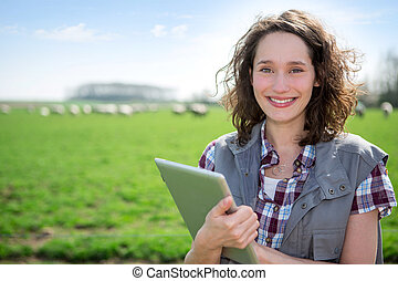 Young attractive farmer in a field using tablet - View of a...