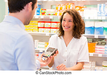 Attractive pharmacist taking healt insurance card - View of...