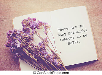 Inspirational motivating quote on notebook and flower with...