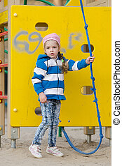 Worried little girl playing on the playground