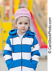 Portrait a four-year girl on background of playground