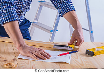 hands of carpenter on table with blueprint plank level...
