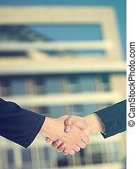 Architectural Handshaking in front of building - Handshake...