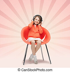 happy little girl listening to music in headphones - people,...