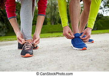 close up of couple tying shoelaces outdoors - fitness,...