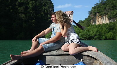 blonde girl speaks with handsome guy sitting on longtail...
