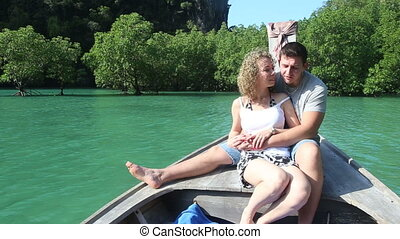 blonde girl and strong handsome guy sitting on longtail boat...