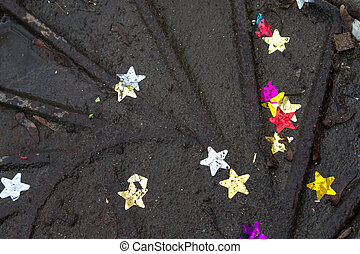 Stars in the Gutter - Coloured stars in dirty water ontop of...