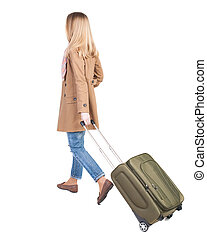 back view of walking woman with suitcase. beautiful girl in...