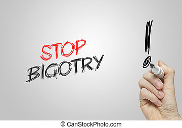 Hand writing stop bigotry on grey background