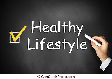 hand writing healthy lifestyle on black chalkboard -...