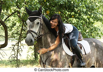 Portrait of beautiful woman and gray horse in garden -...