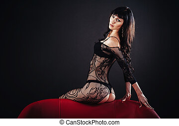Sexy beautiful naked woman in black erotic lingerie on dark background.
