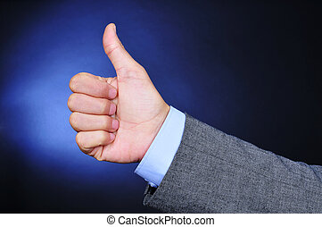 young businessman giving a thumbs-up sign - closeup of the...