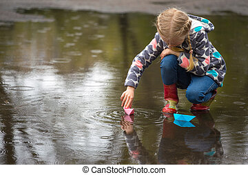 paper boat - girl runs the pink paper boat in a puddle in...