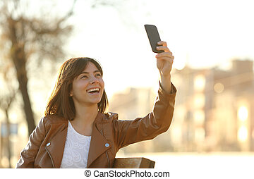 Woman taking selfie photo with a smarphone in winter