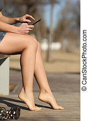 Woman using a smart phone relaxing in a park