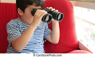 Child looking through binoculars and smiling