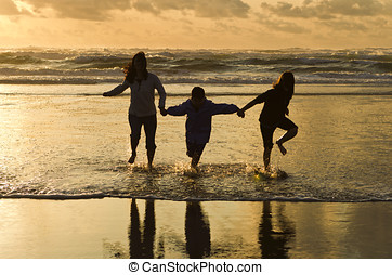 Family runs in the surf at sunset. - A mother, daughter, and...