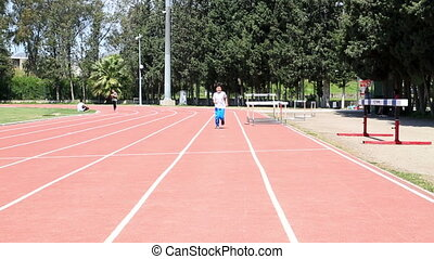 Track Practice - Little boy running outdoor and smiling to...