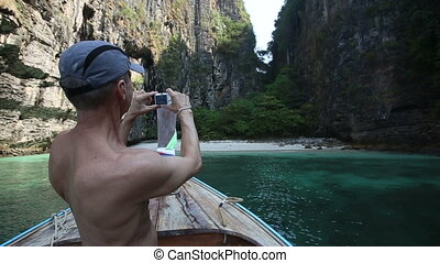 old man photos bay from longtail boat drifting to island -...