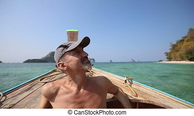 old man drifts in longtail boat to island beach - old naked...
