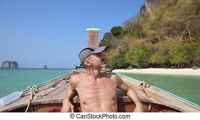 old man sits in longtail boat drifting to island beach