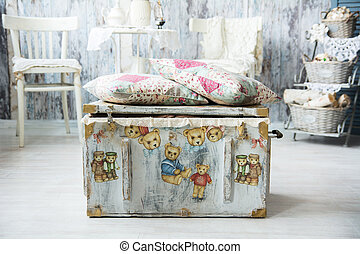 Old chest for toys with painted bears and pillows are...