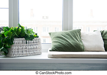 Pillows on the windowsill and plastic window