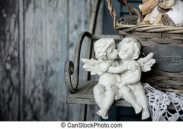 Figurines angels sitting on a bench. Romance on the...